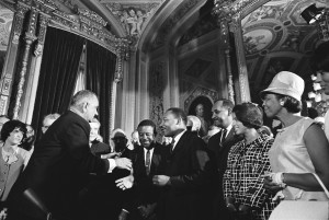 Martin Luther King Jr. and Rosa Parks join President Johnson at the signing of the Voting Rights Act