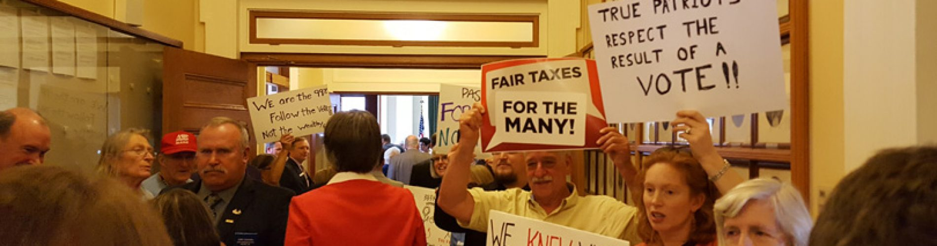 Hundreds are protesting for a fair state budget – here are some of the best signs